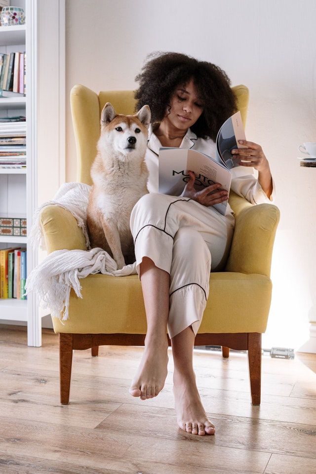 woman reading with dog, experiencing jomo