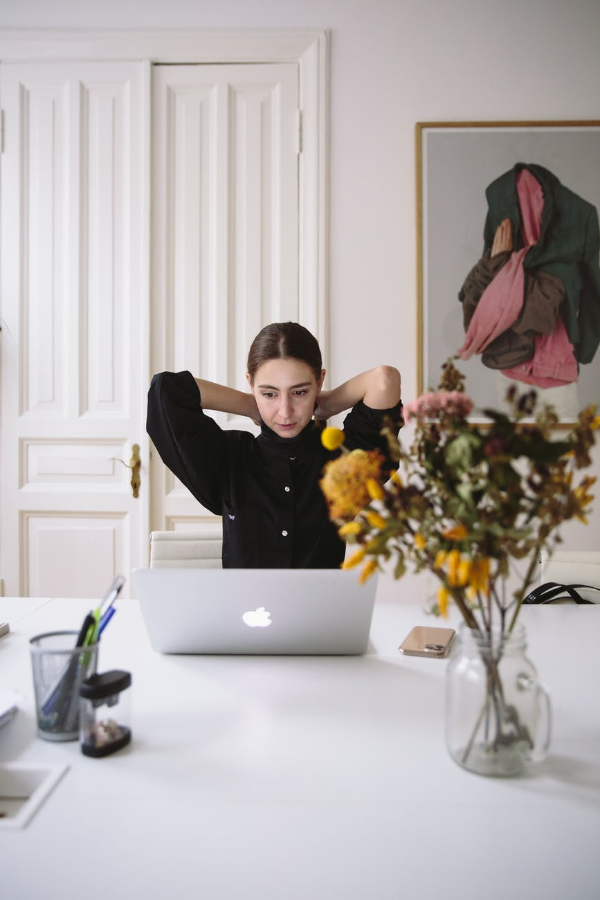 ergonomics when working from home - woman in black blouse sitting in front of silver laptop