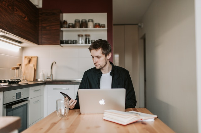 man distracted by phone working from home