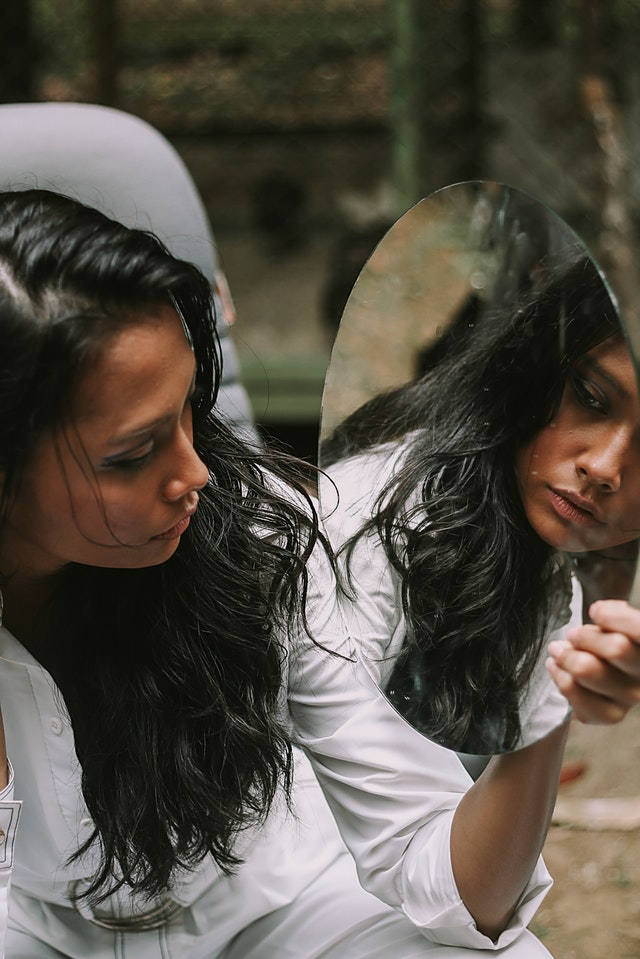 woman looks in mirror self reflection and self awareness
