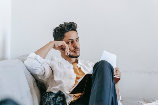 man thinking and journalling on thoughts and feelings